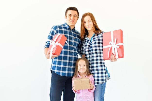 휴일 및 축하 개념 - 흰색 바탕에 크리스마스 선물이 있는 행복한 가족.