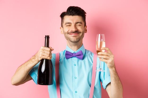 휴일 및 축하 개념. 행복 한 사람 웃 고 파티에서 음주를 즐기고, 샴페인과 유리, 분홍색 배경 위에 서 병을 들고.