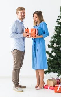 휴일 및 축하 개념 - 여자 친구에게 크리스마스 선물을 주는 남자.