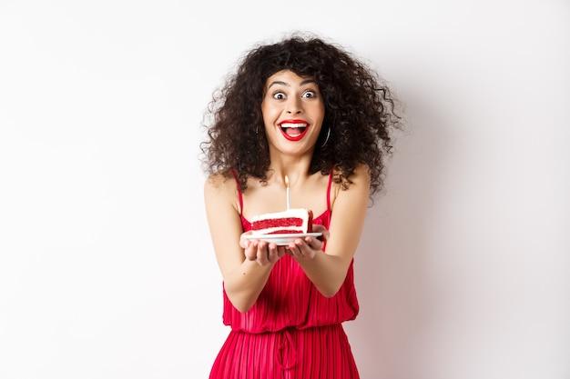 休日とお祝いのコンセプト。白い背景の上に立って、キャンドルであなたにバースデーケーキを与える赤いドレスの笑顔の女性。