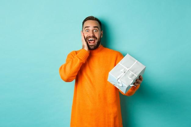 Праздники и концепция празднования. удивленный мужчина получает подарок, выглядит счастливым в настоящее время и улыбается, стоя на синем фоне.