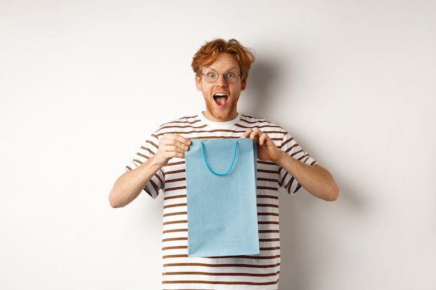 휴일 및 축 하 개념입니다. 놀란 빨간 머리 남자는 쇼핑백 안에 선물을 받고 카메라, 흰색 배경에 놀라고 감사해 보입니다.