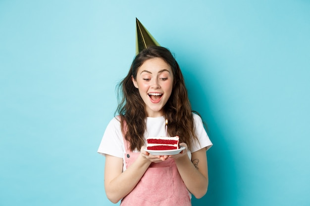 휴일 및 축 하입니다. 생일을 축하하고, 케이크에 촛불을 불고, 파티 케이크를 입고, 즐거운 시간을 보내고, 파란색 배경 위에 서 있는 흥분된 여성.