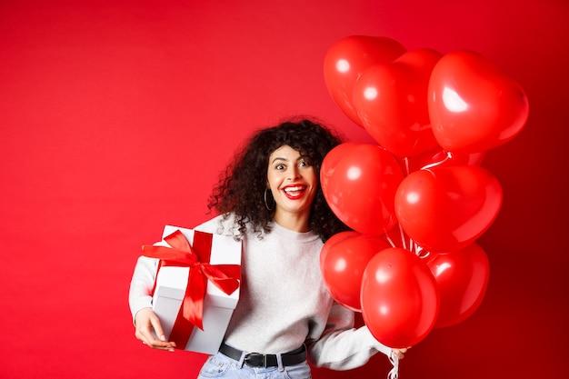 休日やお祝いの誕生日おめでとうの女の子が贈り物を持って、パーティーのヘリウム風船の近くでポーズをとる...