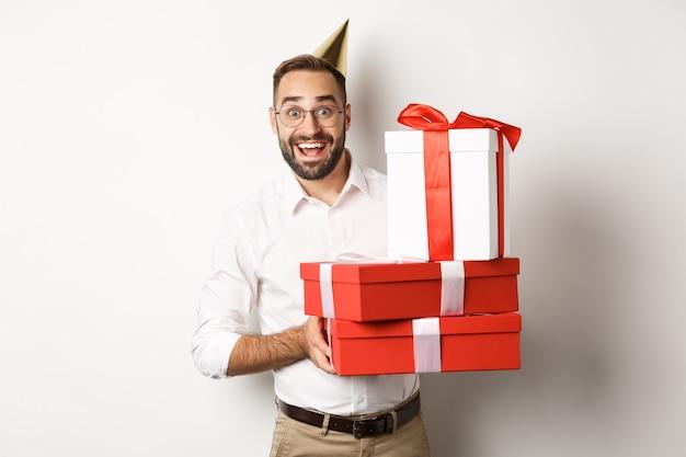 Праздники и торжества. счастливый человек получает подарки на день рождения, держит подарки и выглядит взволнованным, стоя