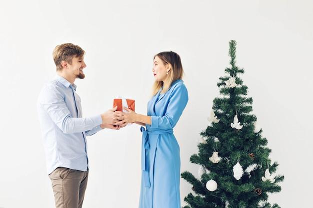 休日やお祝いのコンセプト-クリスマスツリーの前でクリスマスプレゼントを交換するかわいい若いカップル。