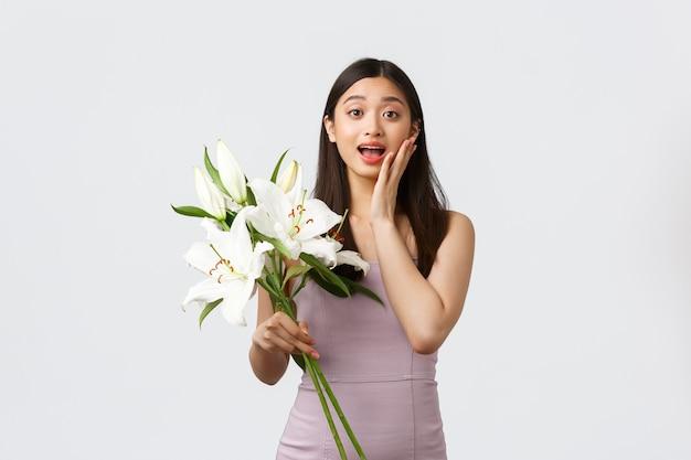休日やイベント、お祝いのコンセプト。イブニングドレスで驚いた幸せなアジアの女の子、秘密の崇拝者から花の花束を受け取り、驚きと感動をあえぎ、ユリを保持し、白い背景