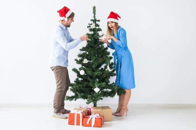 Праздники и праздничная концепция - молодая семейная пара в новогодних шапках, украшающих елку