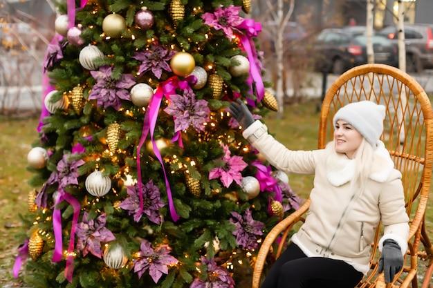 휴일 및 사람들 개념 - 크리스마스 트리 위에 겨울 옷을 입은 젊은 여성