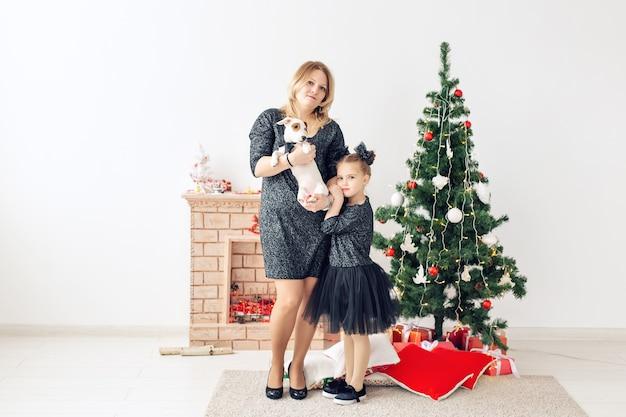 Праздники и концепция домашних животных - мать и дочь, играя с собакой джек-рассел-терьер перед рождественской елкой дома.