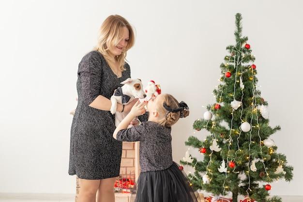 Праздники и концепция домашних животных - мать и дочь играют с собакой джек-рассел-терьера перед