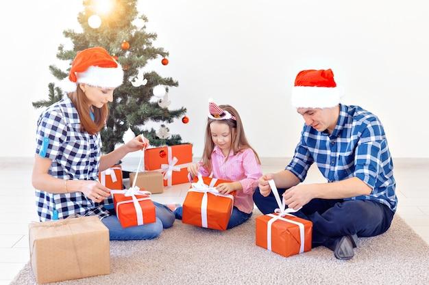 休日とプレゼントのコンセプト-クリスマスの時期に贈り物を開く幸せな家族の肖像画。