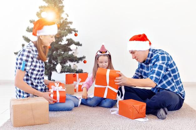 휴일 및 선물 개념 - 크리스마스 때 선물을 여는 행복한 가족의 초상화.