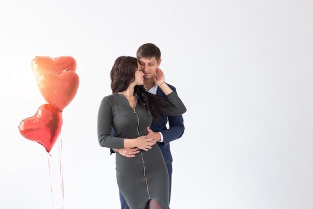 休日と関係の概念-コピースペースと白い背景の上のバレンタインデーの若いカップル