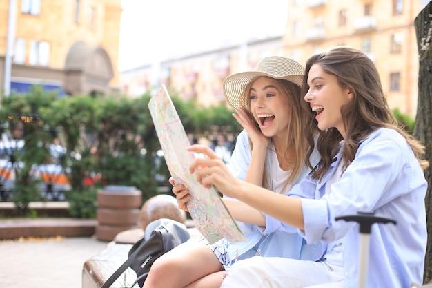 휴일 및 관광 개념 - 도시에서 방향을 찾는 아름다운 소녀들.