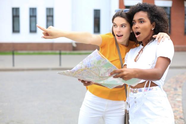 Концепция праздников и туризма - красивые девушки ищут направление в городе.