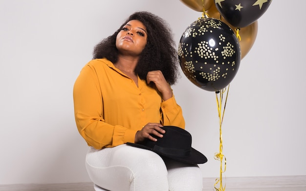 休日、誕生日パーティー、楽しいコンセプト-風船を保持している白い背景でスタイリッシュに見える笑顔の若いアフリカ系アメリカ人の若い女性の肖像画。
