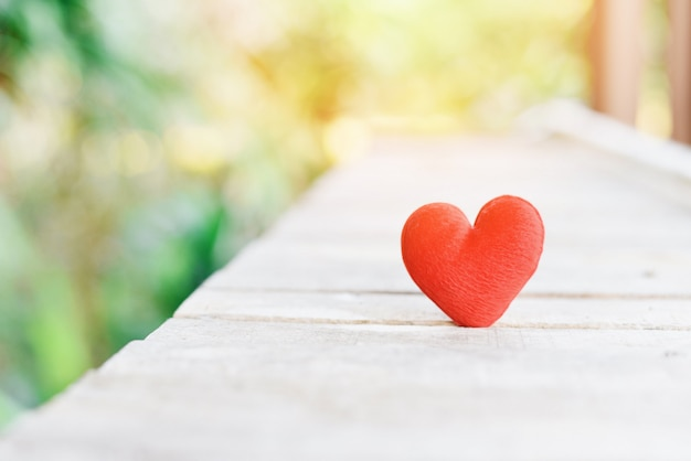 祝日カード慈善の概念の夕日と古い木のバレンタインの赤いハート-木製の背景に心を寄付愛を与える Premium写真