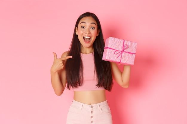 休日、お祝い、ライフスタイルのコンセプトです。ピンクの壁の上に立って、ギフトボックスの内側を推測し、現在を指して、陽気な笑顔で驚いて、興奮して、幸せなアジアの女の子。