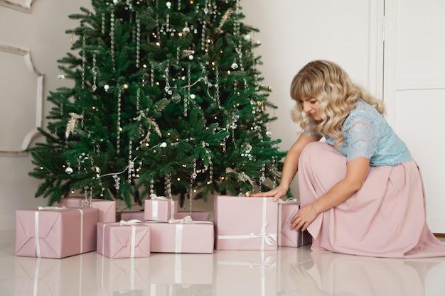 休日のお祝いと人々はクリスマスのインテリアの背景にエレガントなドレスで若い女性を概念します。
