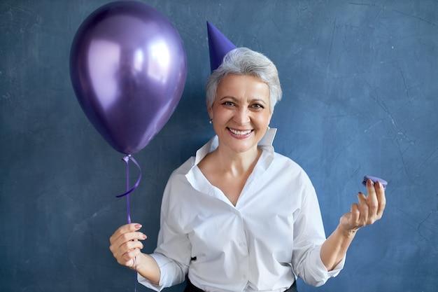 休日、お祝い、特別な行事のコンセプト。ヘリウム気球を保持しているお祝いの服を着た感情的な面白い白人女性年金受給者の肖像画