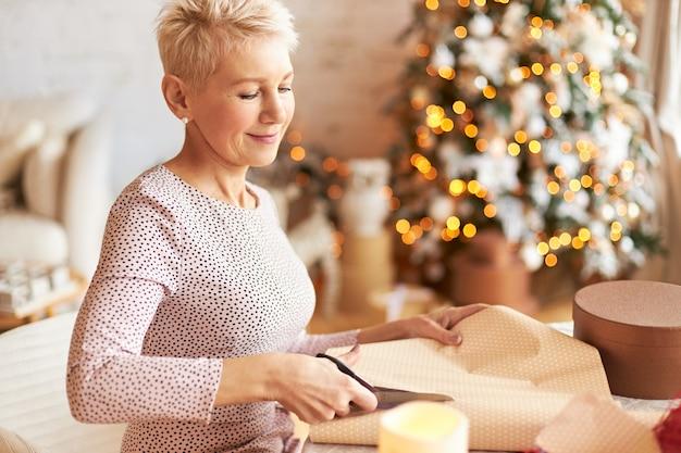 휴일, 축하 및 휴가 개념. 크리스마스 트리 장식 된 거실에서 포즈를 취하는 짧은 머리를 가진 우아한 아름다운 성숙한 여인, 가위로 선물 포장 절단