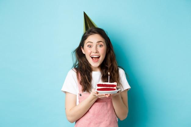 Vacanze e celebrazione. ragazza allegra di compleanno in cappello da festa che tiene la torta di compleanno e sorride, esprimendo desiderio sulla candela accesa, in piedi su sfondo blu.