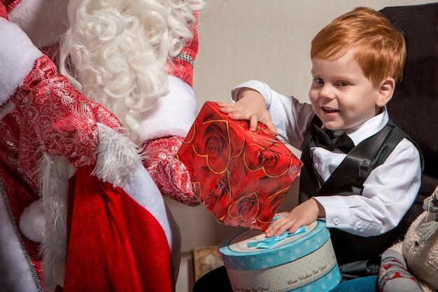 Праздники, праздник, детство и люди концепции. улыбающийся маленький мальчик с дедом морозом