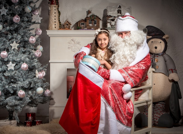 Holidays, celebration, childhood and people concept - smiling little girl with santa claus over christmas tree  background