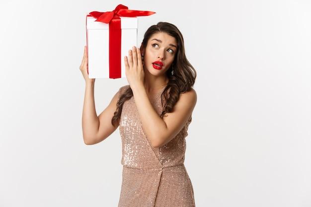 Праздники, концепция празднования. красивая женщина в роскошном платье пытается угадать, что внутри подарочной коробки, тряся рождественский подарок с любопытным лицом, на белом фоне.