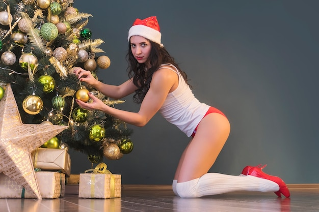 Holidays and celebration concept - happy brunette woman in santa's hat decorates a christmas tree at home in the living room, red pants