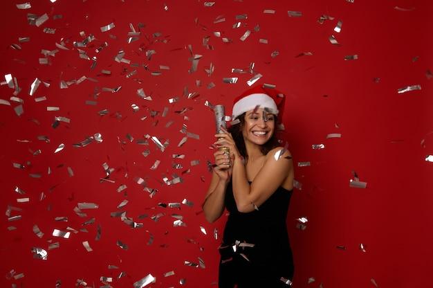 휴일 축 하 개념입니다. 산타 모자를 쓰고 크리스마스 파티에서 장식 조각과 색종이 조각이 있는 이브닝 블랙 드레스를 입은 행복한 젊은 혼혈 아름다운 여성. 새해 축하, 빨간색 배경, 복사 공간