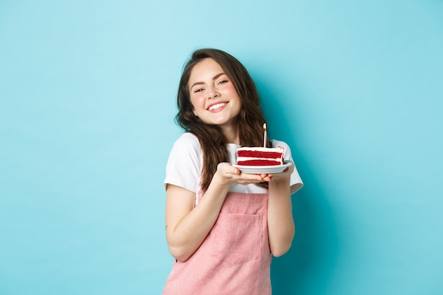 Holidays and celebration. cute glamour girl celebrating her birthday, holding plate with cake and smiling cheerful, celebrating, standing over blue background.