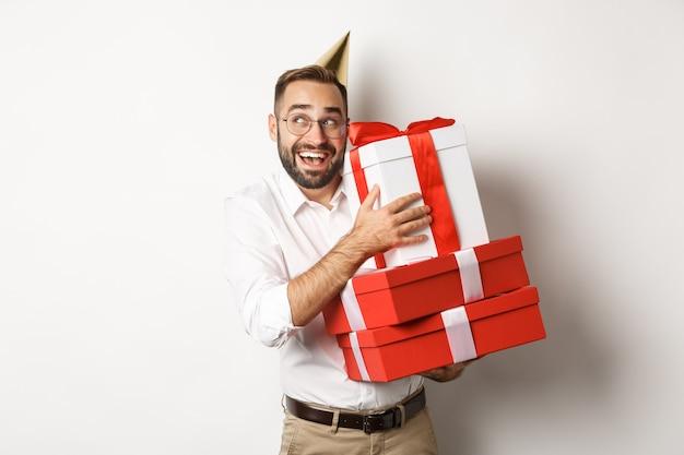 Feste e celebrazioni. uomo eccitato che ha festa di compleanno e che riceve regali, che sembra felice, in piedi