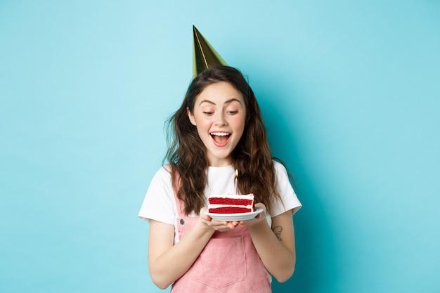 Vacanze e celebrazione. donna eccitata che festeggia il compleanno, soffia una candela sulla torta, indossa una torta da festa e si diverte, in piedi su sfondo blu.