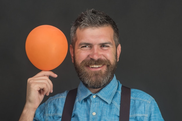 Празднование праздников с днем рождения и концепция образа жизни улыбающийся человек с оранжевым воздушным шаром летом