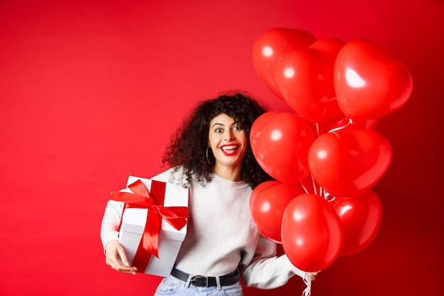 Holidays and celebration happy birthday girl holding gift and posing near party helium balloons smil...
