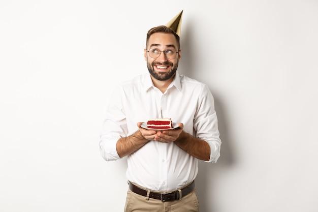 Feste e celebrazioni. uomo felice che ha festa di compleanno, esprimere il desiderio sulla torta b-day e sorridente, in piedi