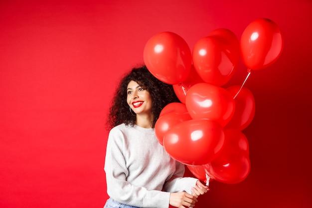 Vacanze e celebrazione donna felice in posa con palloncini festa su sfondo rosso guardando da parte a e...