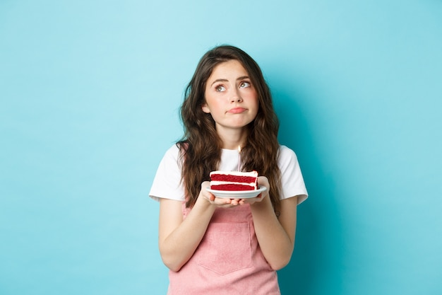 Vacanze e celebrazione. donna triste e cupa che tiene la torta di compleanno, distogliendo lo sguardo con la faccia pensosa sconvolta, in piedi su sfondo blu.