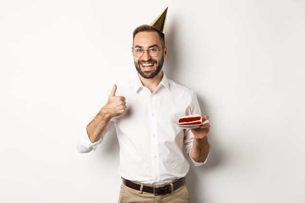 Feste e celebrazioni. uomo soddisfatto che gode della festa del b-day, che tiene la torta di compleanno e che mostra il pollice in su in approvazione, consigliando qualcosa, fondo bianco.