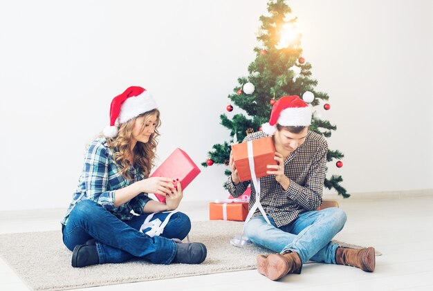 휴일, 크리스마스 및 가족 개념 - 집에서 선물을 여는 젊은 행복한 커플.