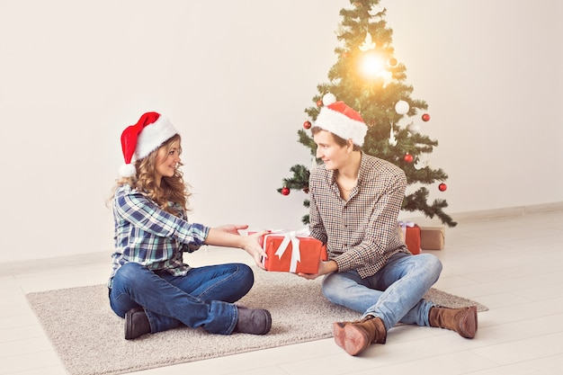 Праздники, рождество и концепция семьи - молодые счастливые пары открытия подарков дома.