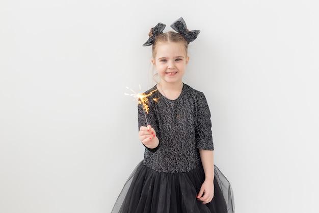 休日、クリスマス、新年のコンセプト-幸せな子供はコピースペースで白い背景の上に彼女の手で燃える線香花火を保持します。