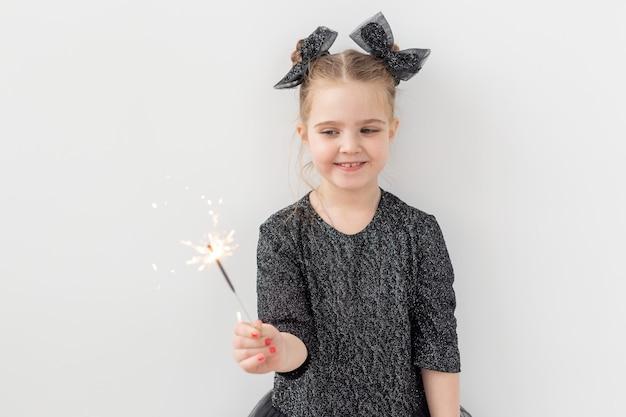 休日、クリスマス、新年のコンセプト-幸せな子供はコピースペースで白い背景の上に彼女の手で燃える線香花火を保持します。 Premium写真