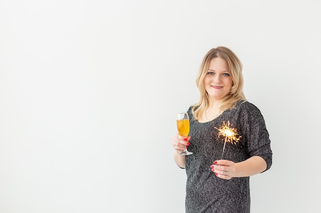 休日、クリスマス、誕生日、新年のコンセプト-女性は祝うと白い背景、クローズアップの上のガラスと線香花火でワインを保持します。