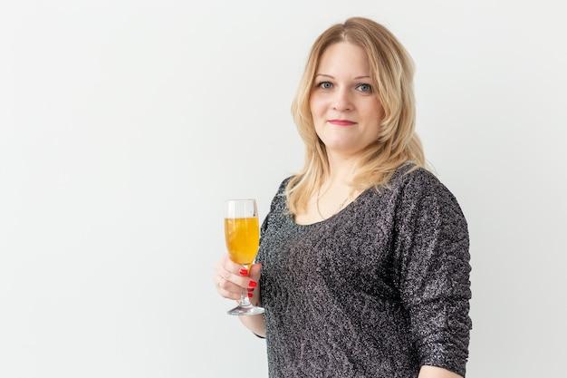 休日、クリスマス、誕生日、新年のコンセプト-女性は白い背景の上にグラスと線香花火でワインを祝い、保持します。