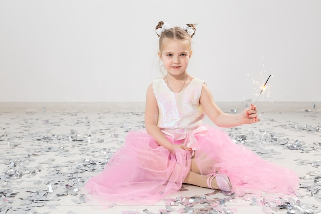 Holidays, christmas, birthday party and new year concept - child holding burning sparkler. after funny party.