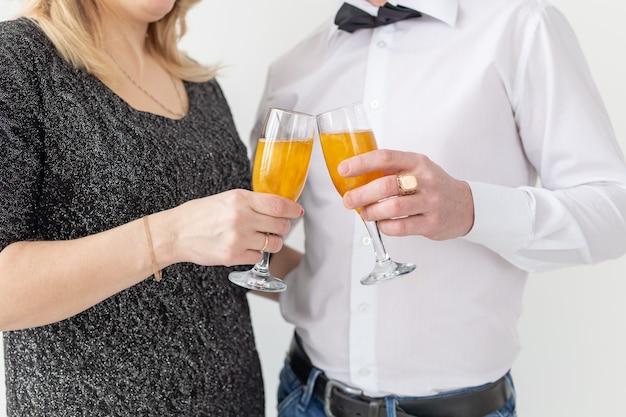 휴일, 크리스마스, 발렌타인 데이 및 새해 개념 - 여자와 남자는 흰색 배경 위에 유리 클로즈업으로 와인을 축하하고 보유합니다.