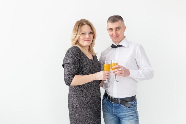 휴일, 크리스마스, 발렌타인 데이 및 새해 개념 - 여성과 남성은 복사 공간이 있는 흰색 배경 위에 와인을 축하하고 보유합니다